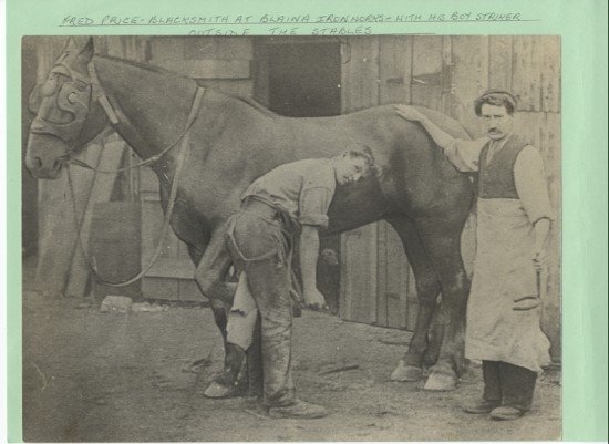 Fred Price, Blacksmith at Blaina Ironworks, with his boy striker outside the stables